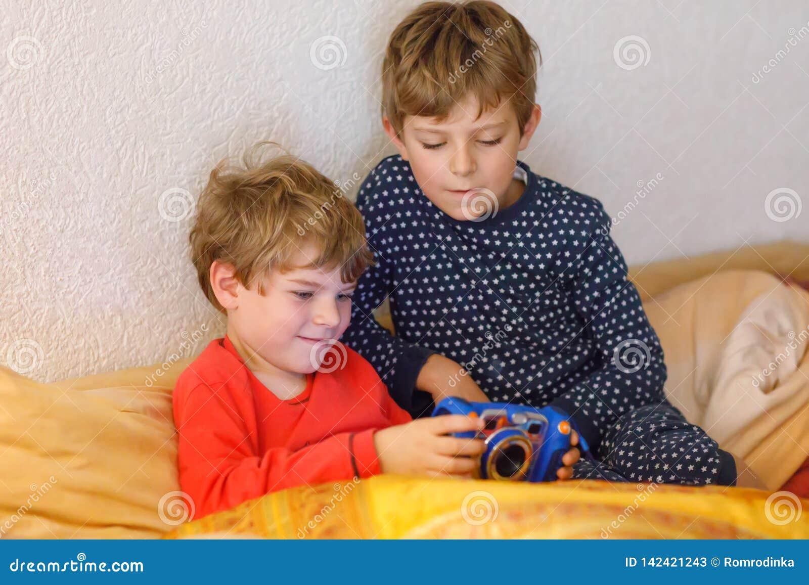 Dwa preschool, szkolne dzieciak chłopiec, rodzeństwa lub bracia ma zabawę po dnia powszedniego bawić się gra wideo w domu, i