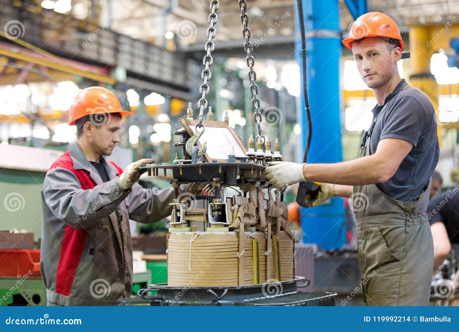 Dwa przemysłowego pracownika gromadzić władza transformator przy konwejer fabryki warsztatem