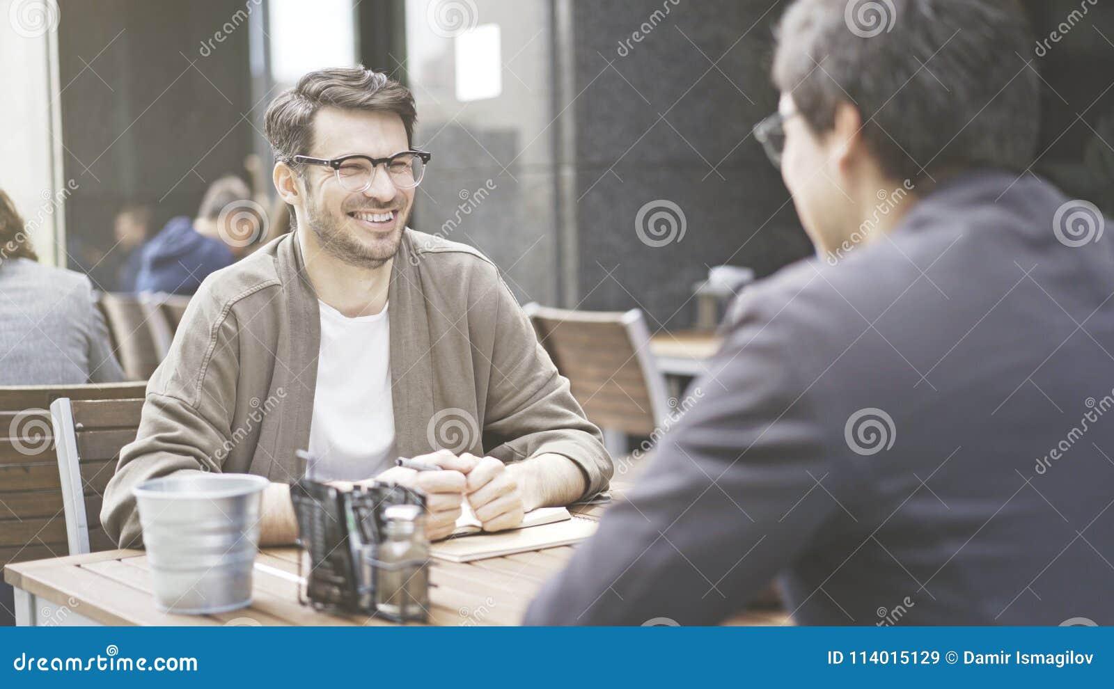 Dwa przyjaciela są roześmiani przy stołem kawiarnia outdoors