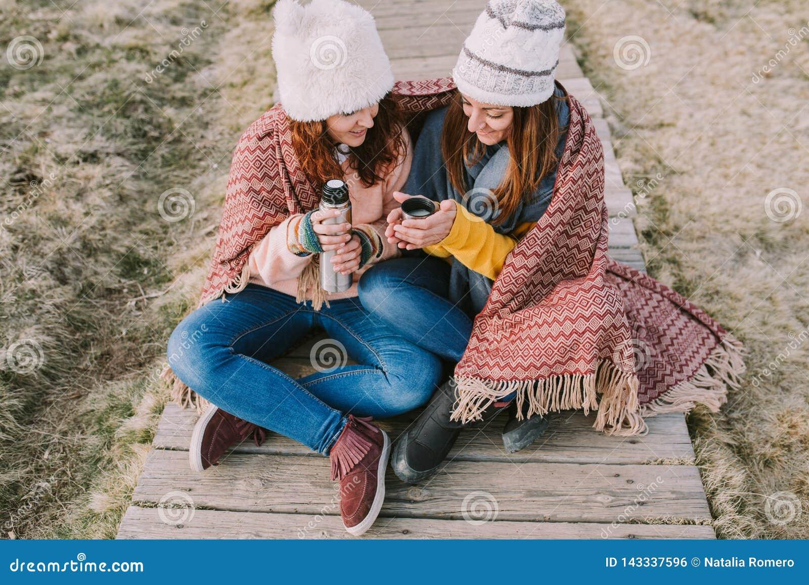 Dwa przyjaciela zawijającego w koc siedzą w łące podczas gdy biorą za termosie przygotowywać rosół