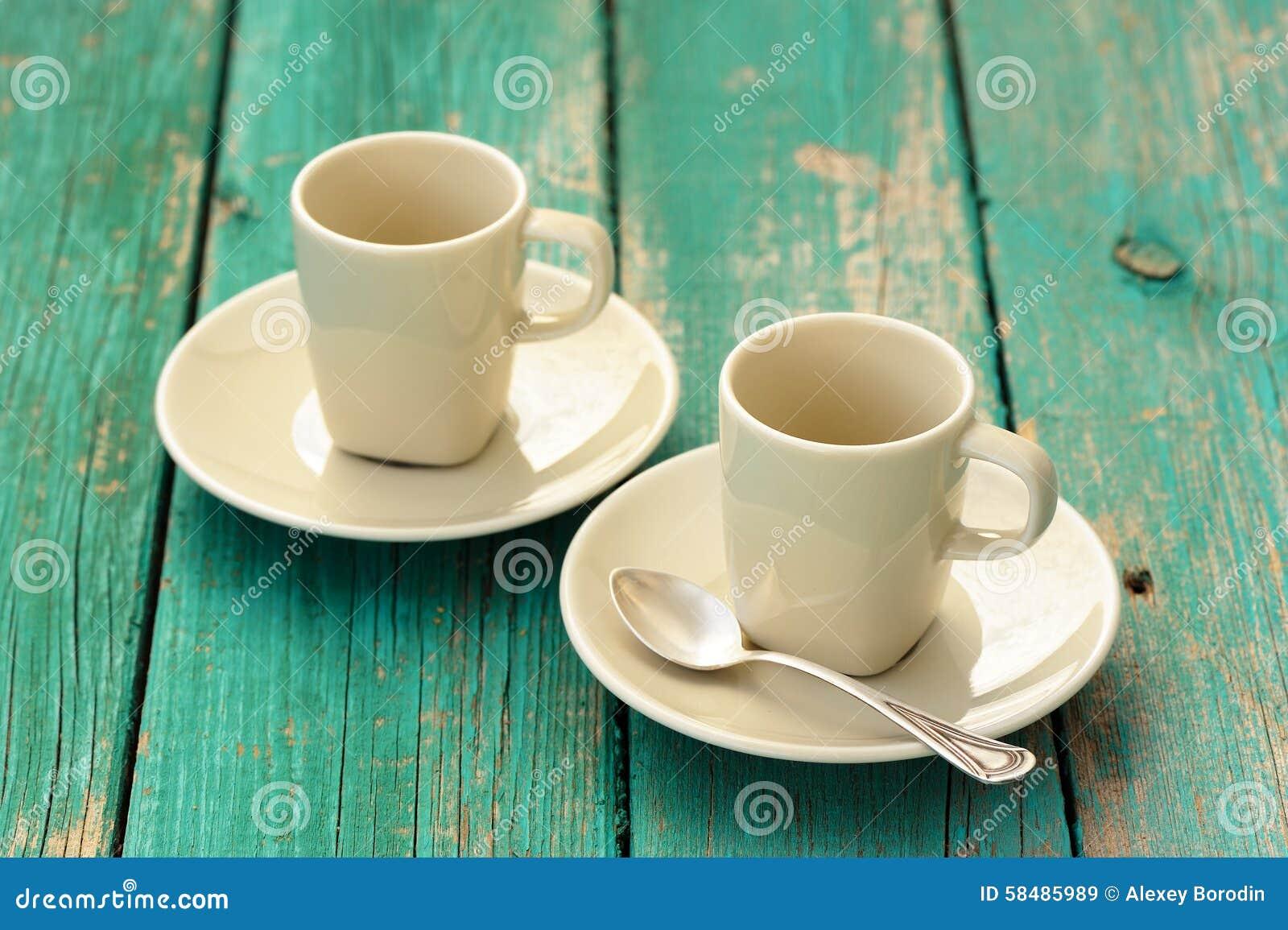 Dwa pustej heban kawy espresso filiżanki z srebną łyżką na turkusowym sha