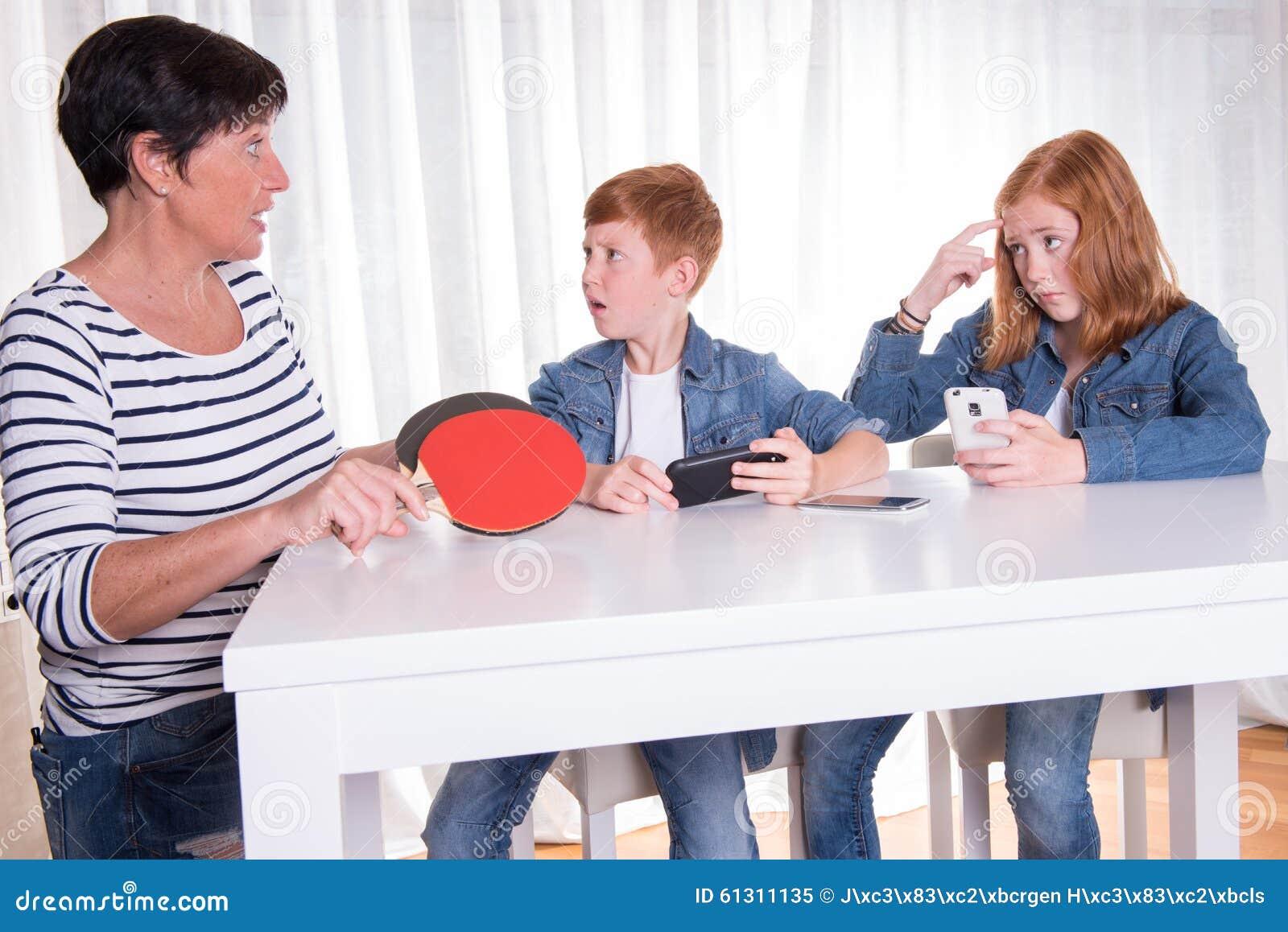 Dwa redhaired dzieciaka bawić się z ich smartphones macierzystym wa
