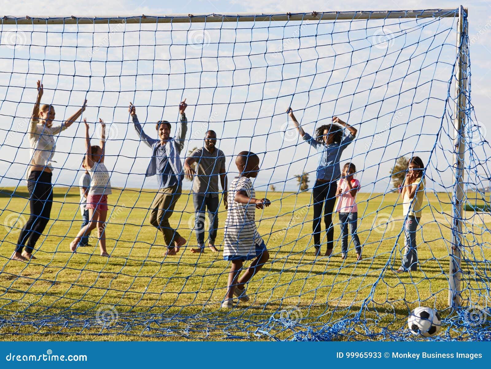 Dwa rodziny bawić się futbol w parku świętuje cel
