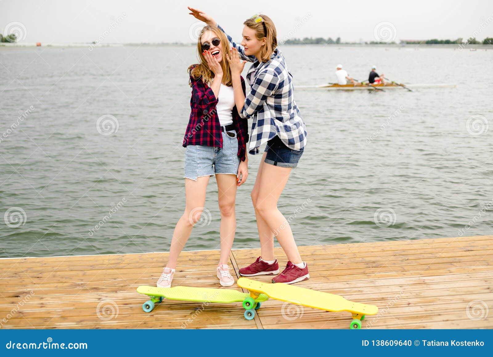 Dwa rozochoconej szczęśliwej łyżwiarki dziewczyny w modnisia stroju ma zabawę na drewnianym molu podczas wakacje