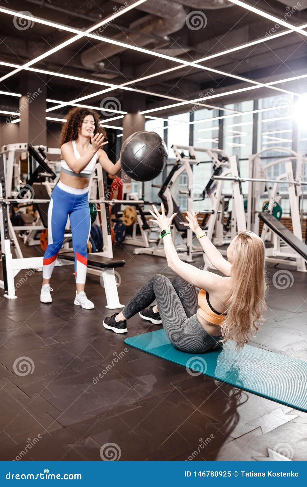 Dwa sportowej dziewczyny ubieraj?cej w sportswear robi? ?wiczeniom dla prasy na macie dla sprawno?ci fizycznej z sprawno?ci fizyc