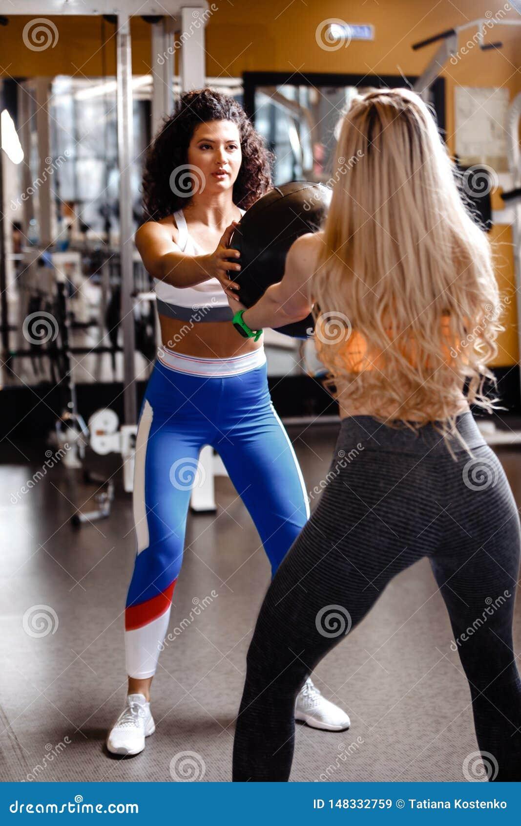 Dwa sportowej dziewczyny ubieraj?cej w sportswear robi? wp?lnie tylnym kucni?ciom z ci??k? sprawno?ci fizycznej pi?k? w nowo?ytny