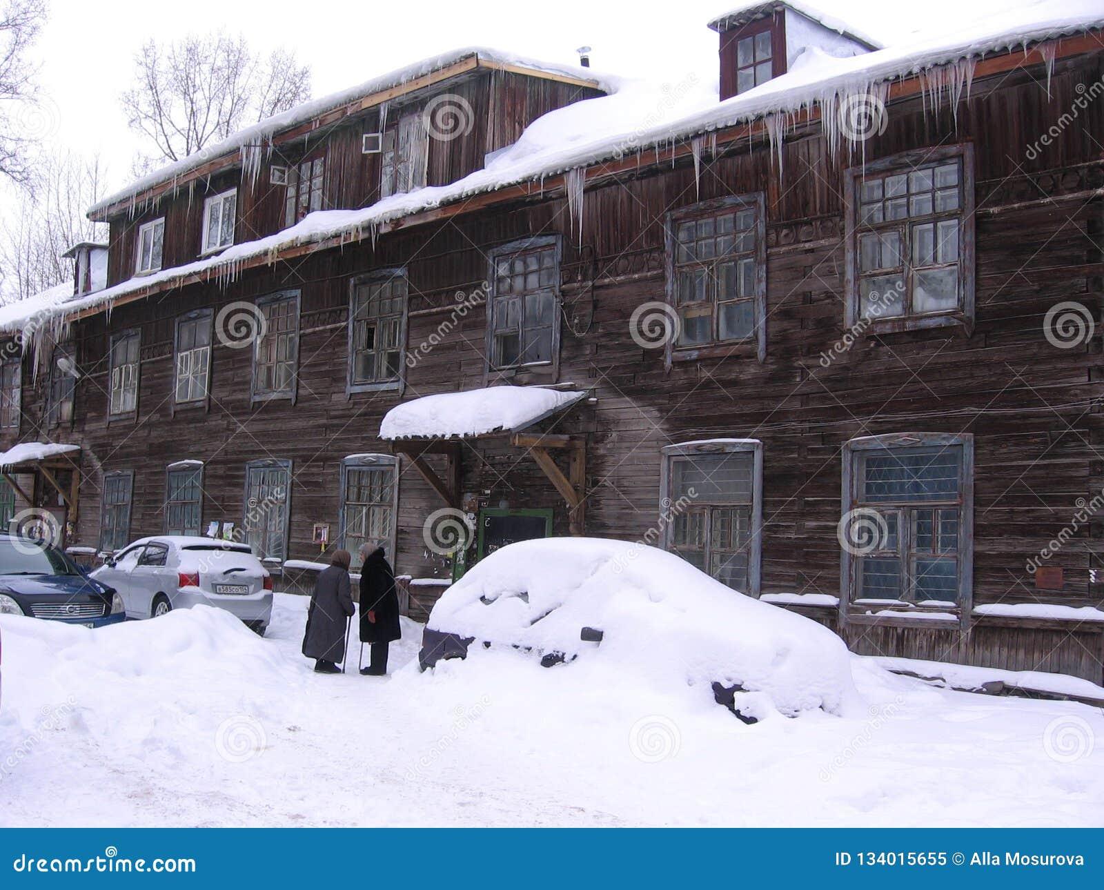 Dwa starej kobiety opowiada w zimie blisko wielkiego drewnianego domu