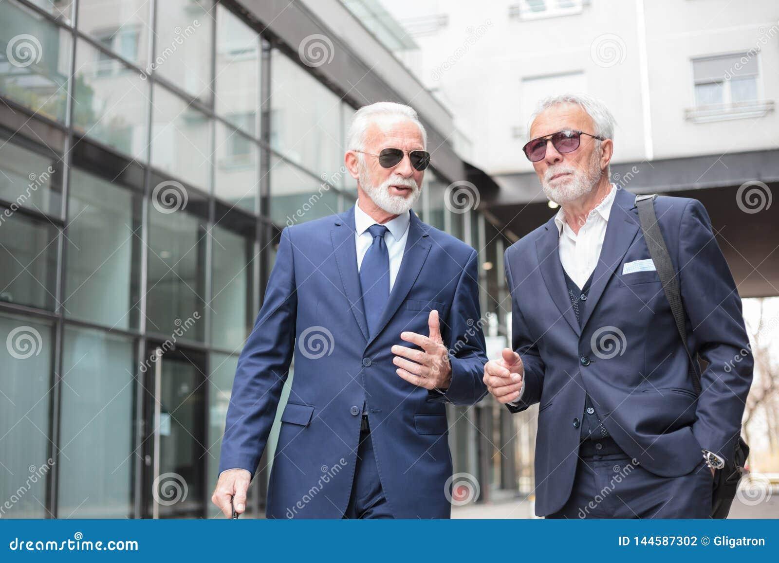 Dwa starszego biznesmena chodzi w dół ulicę, dyskutuje