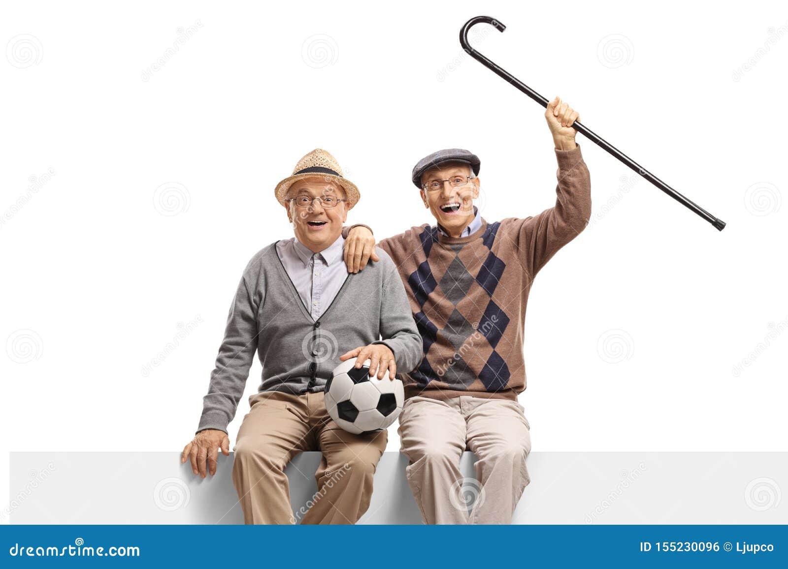 Dwa starszego mężczyzny z futbolem sadzającym na panelu