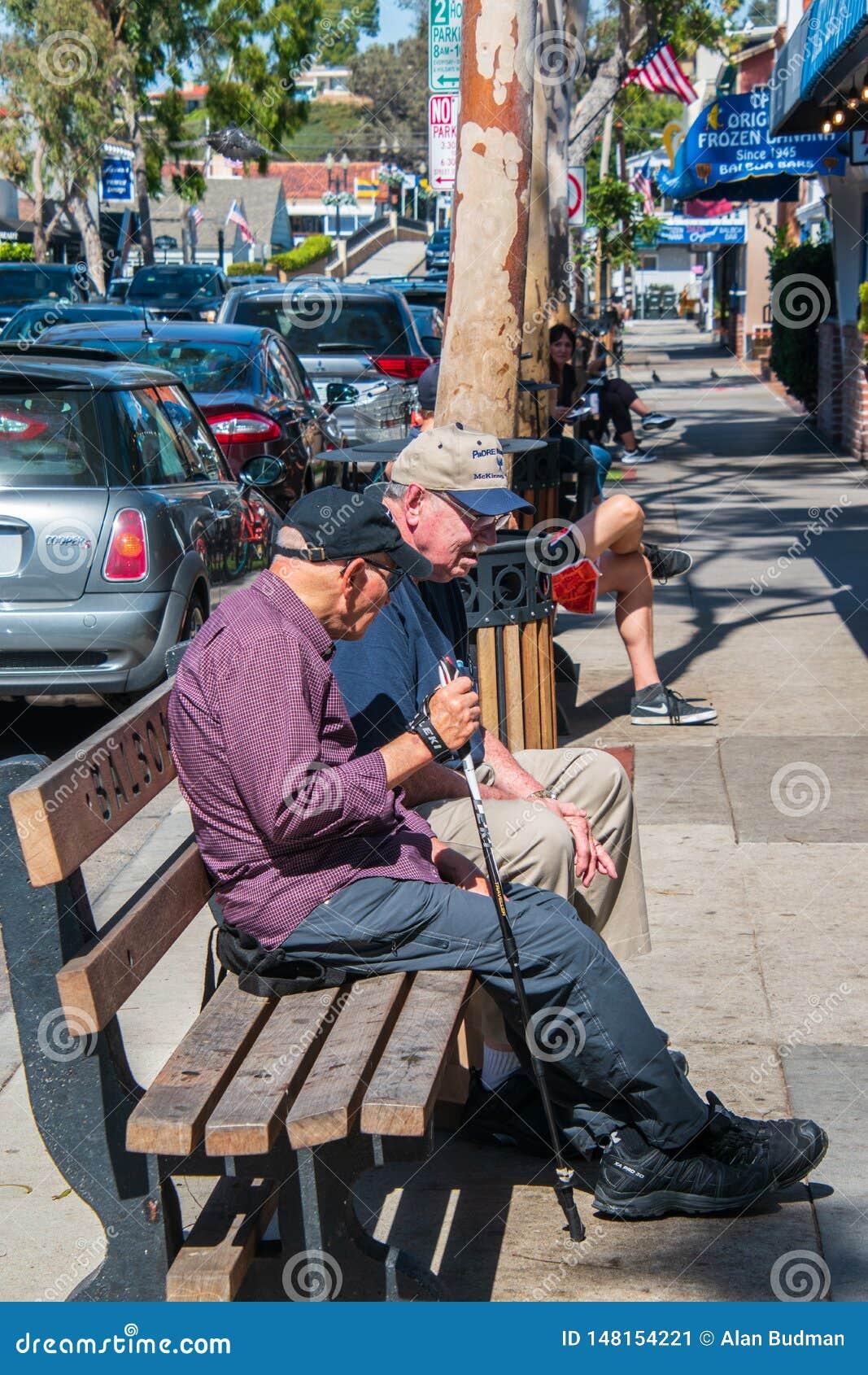 Dwa starszego obywatela caucasian męskiego przyjaciela na ławce w zakupy okręgu balboa wyspa