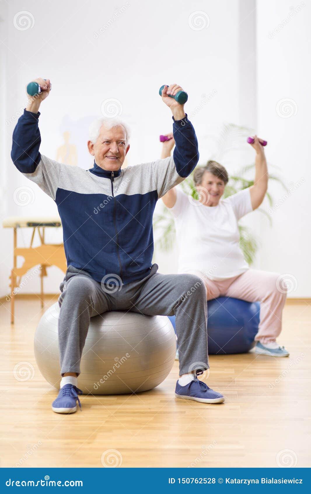Dwa starszego pacjenta ćwiczy z ciężarami w centrum rehabilitacji