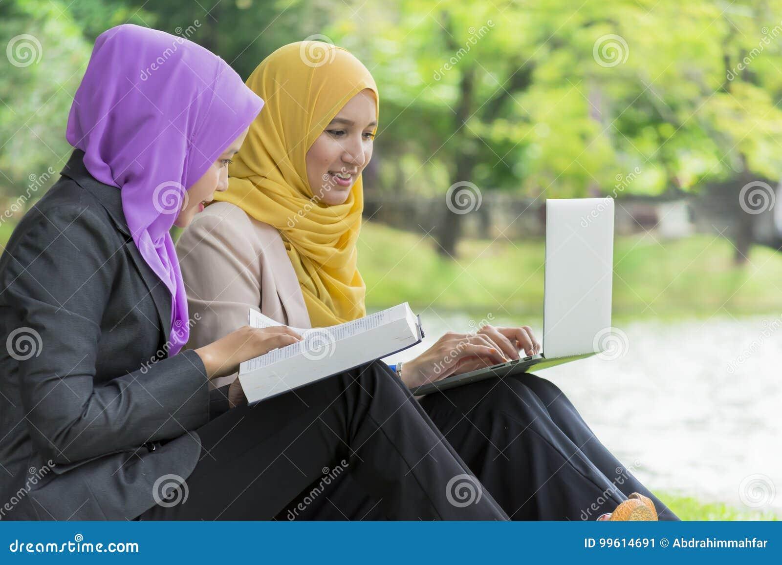 Dwa studenta collegu ma dyskusję i zmienia pomysły w parku podczas gdy siedzący