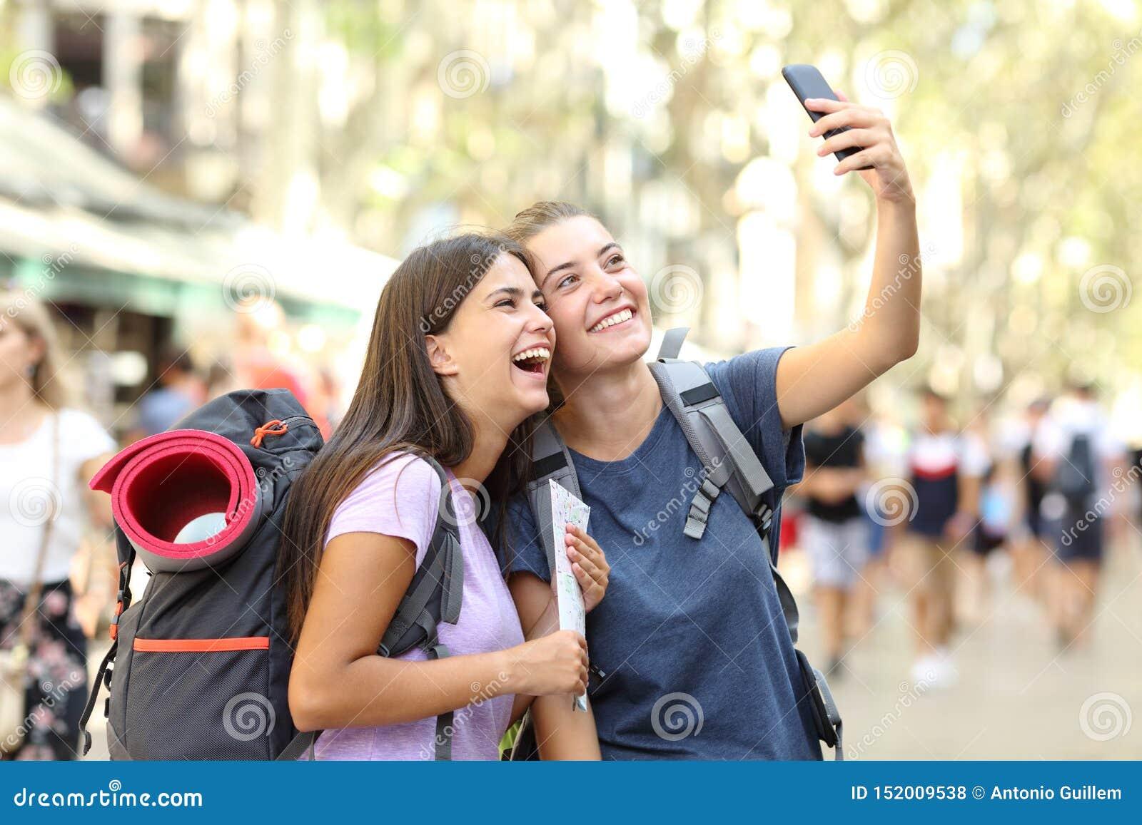 Dwa szczęśliwego backpackers bierze selfies w ulicie na wakacje