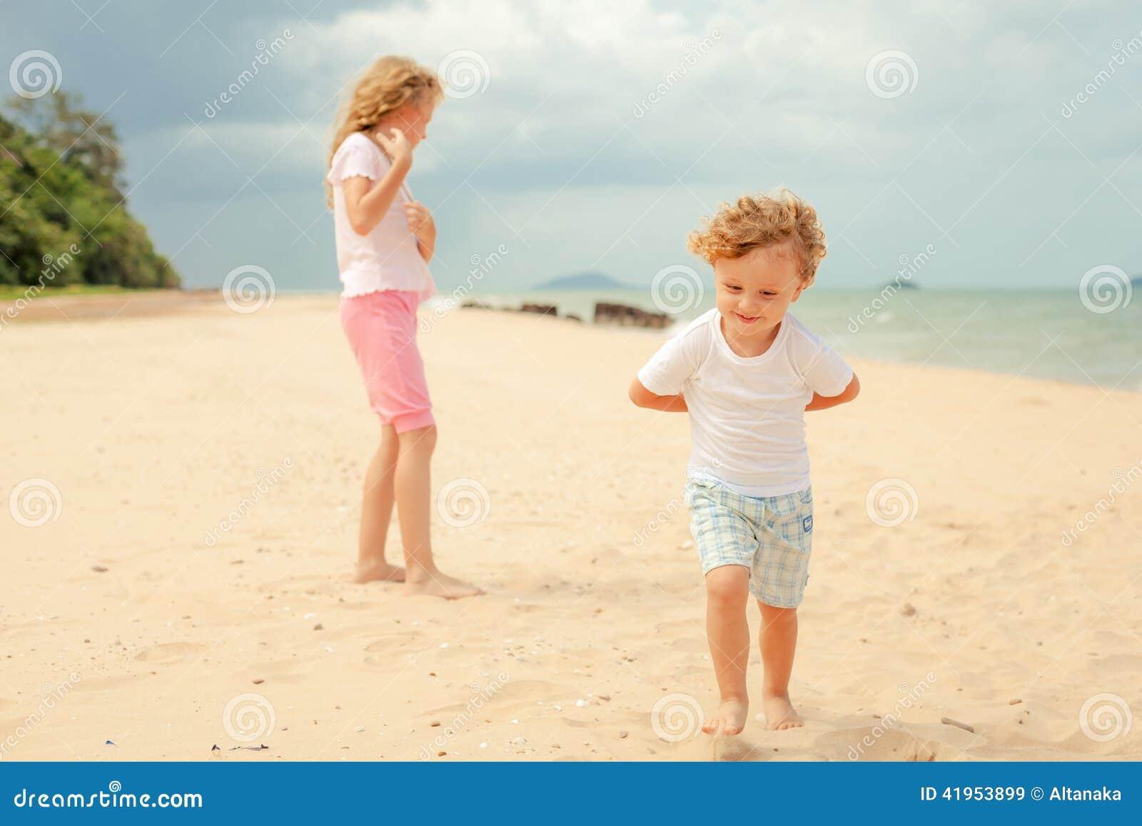 Dwa szczęśliwego dzieciaka bawić się przy plażą