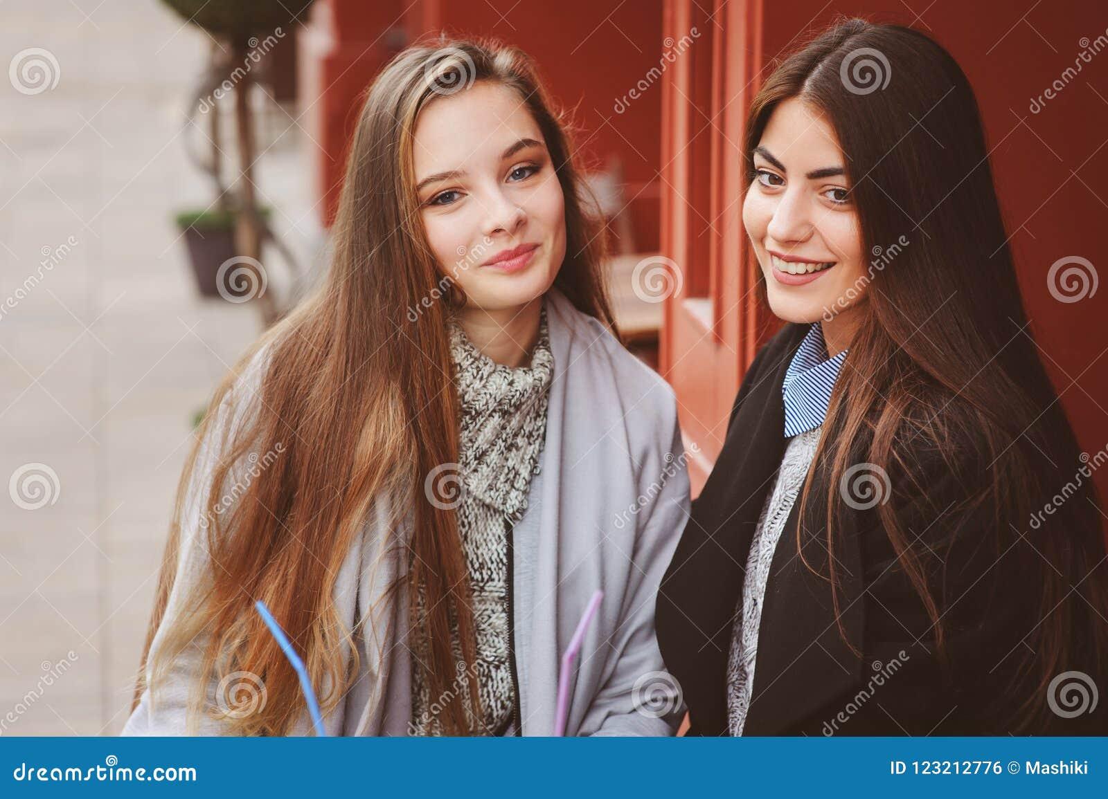Dwa szczęśliwego dziewczyna przyjaciela opowiada kawę w jesieni mieście w kawiarni i pije