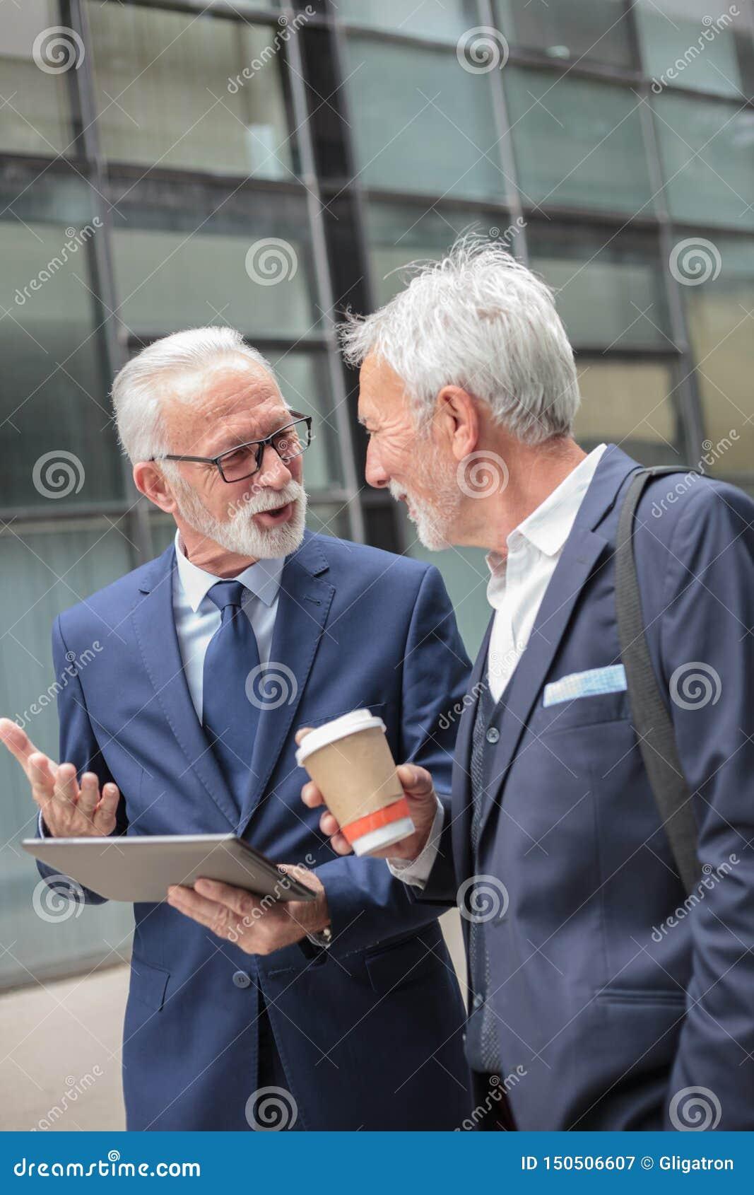 Dwa szczęśliwego starszego szarego włosianego biznesmena chodzi wzdłuż ulicy podczas kawowej przerwy