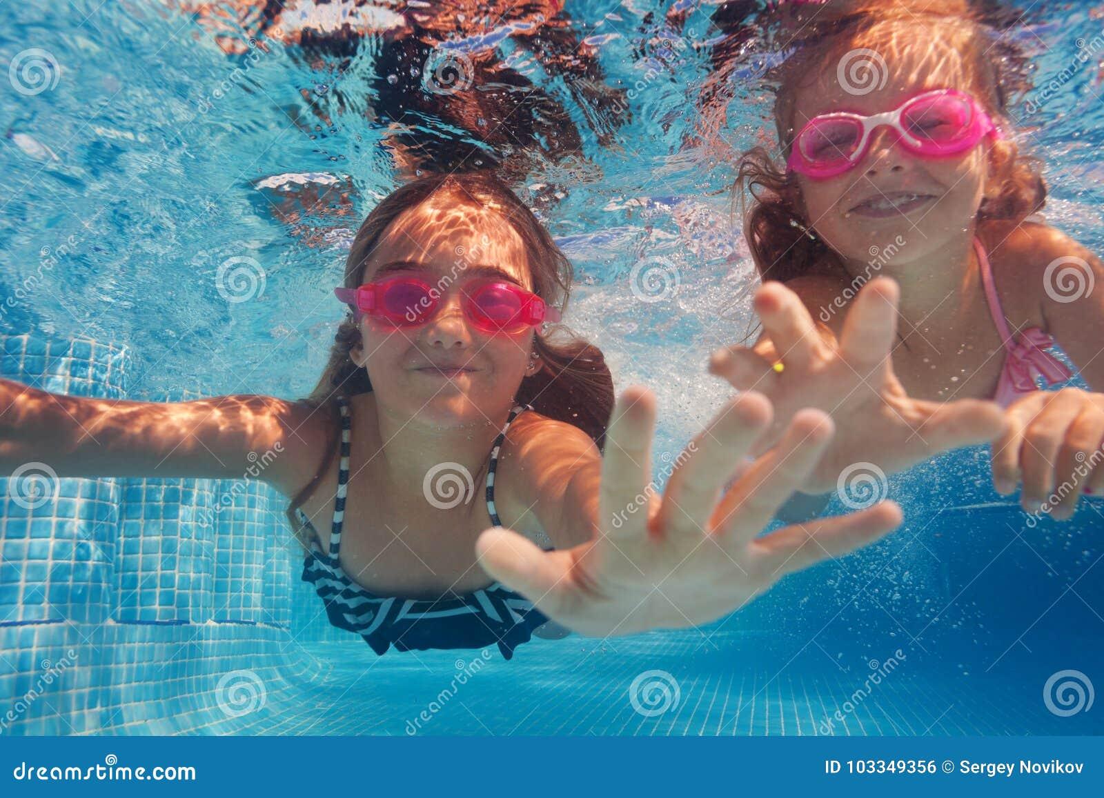 Dwa szczęśliwej dziewczyny pływa pod wodą w gogle