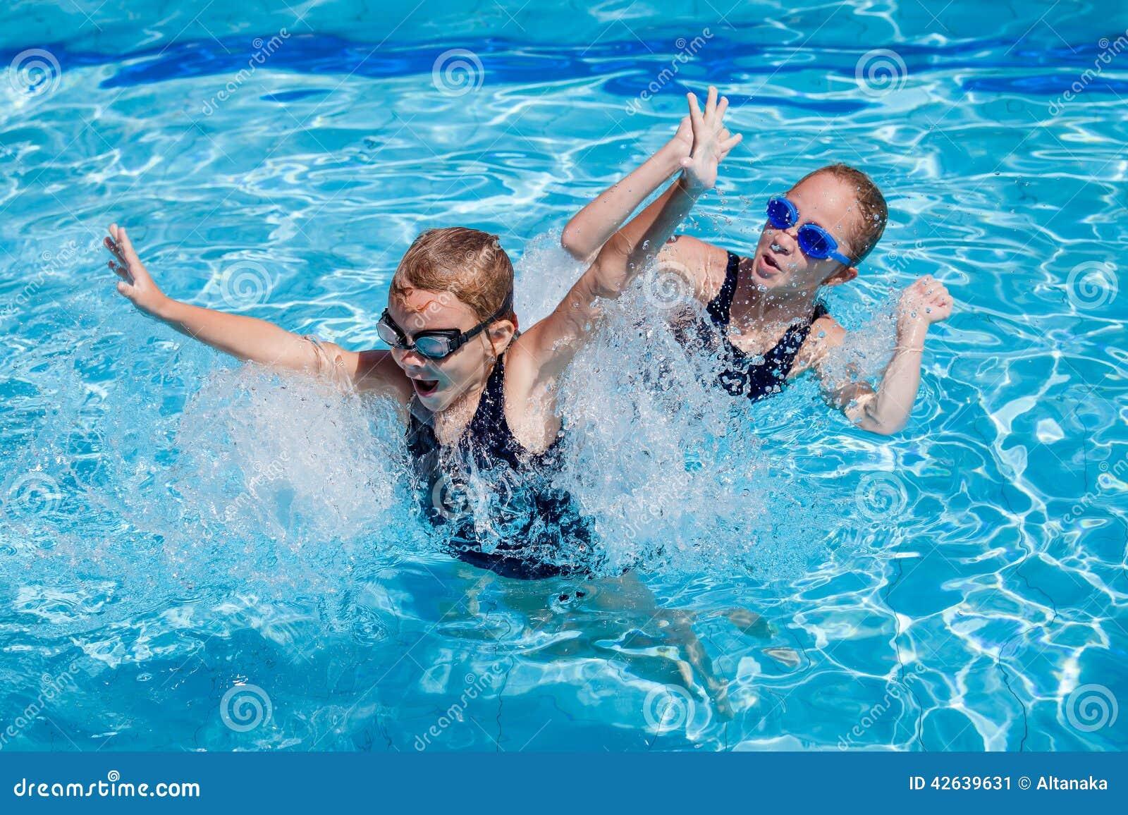 Dwa szczęśliwej małej dziewczynki bawić się w pływackim basenie