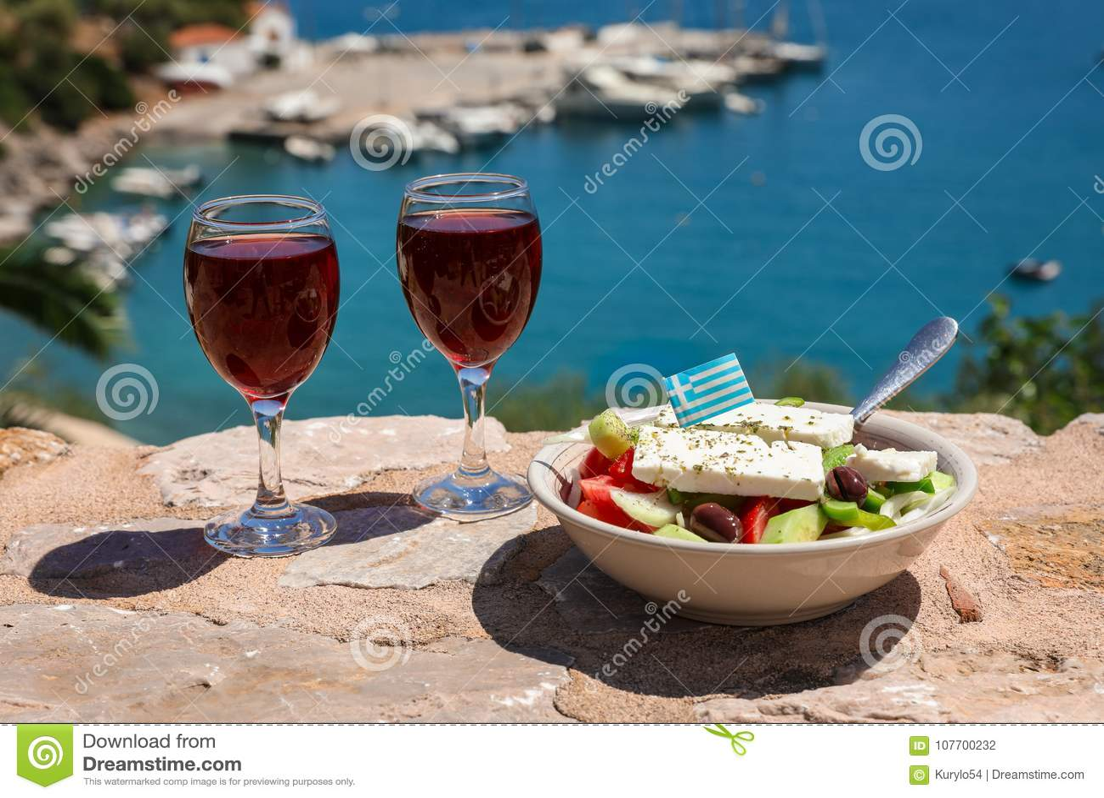 Dwa szkła czerwone wino i puchar grecka sałatka z grkiem zaznaczają dalej dennym widokiem, lato wakacji grecki pojęcie