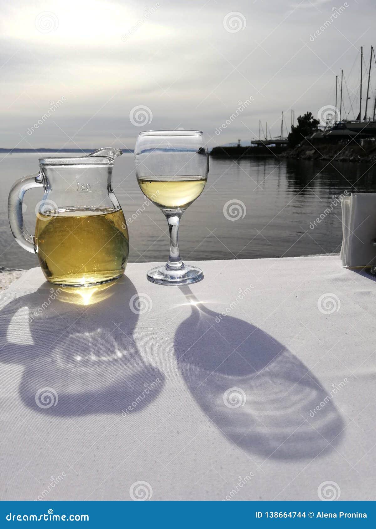 Dwa szklany blisko morza i wyszczerbienie z białym winem na stole