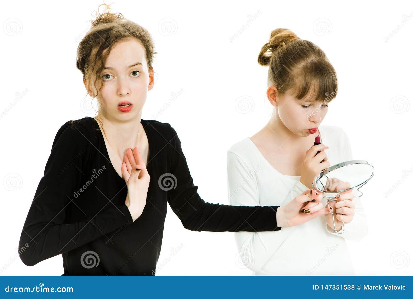 Dwa teenaged dziewczyny targują się dostawać lustro robić uzupełniającemu - siostrzana rywalizacja