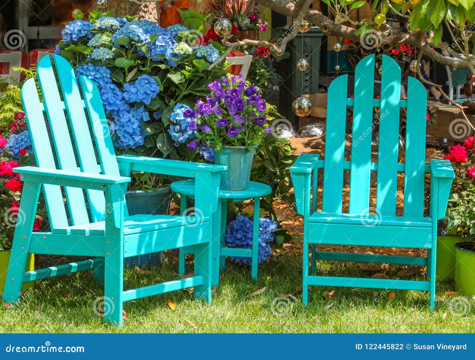 Dwa turkusu Adirondack krzesła i dopasowywanie stół otaczający pięknymi kwiatami, drzewami i jaśnienie lustrzanymi piłkami wręcza