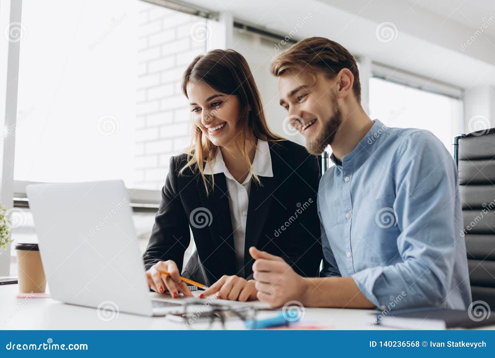 Dwa uśmiechniętego biznesmena siedzi wpólnie przy stołem w nowożytnym biurze opowiada laptop i używa