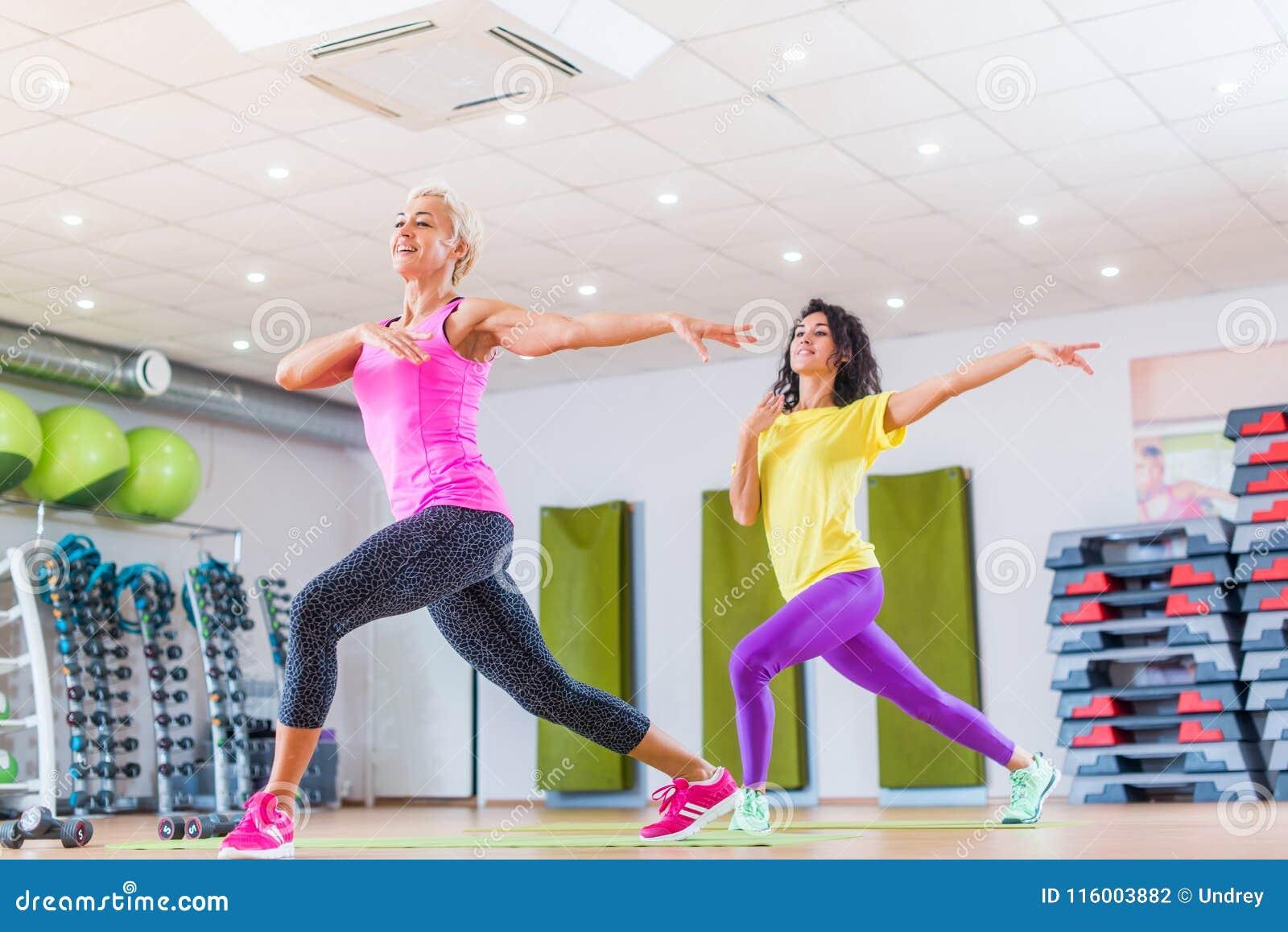 Dwa uśmiechnięta żeńska sprawność fizyczna modeluje pracującego out w gym lub studiu robi cardio ćwiczeniu, dancingowy zumba