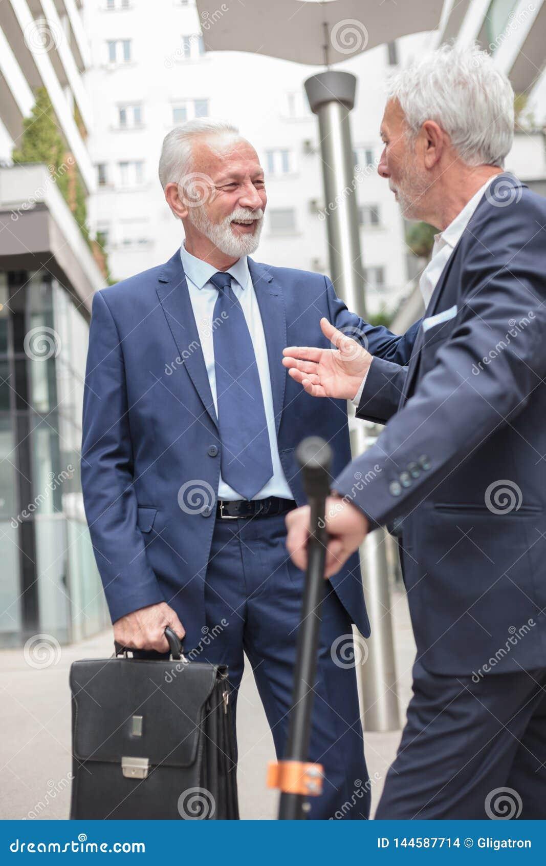 Dwa uśmiechniętego starszego biznesmena spotyka i opowiada na chodniczku, otaczającym budynkami biurowymi