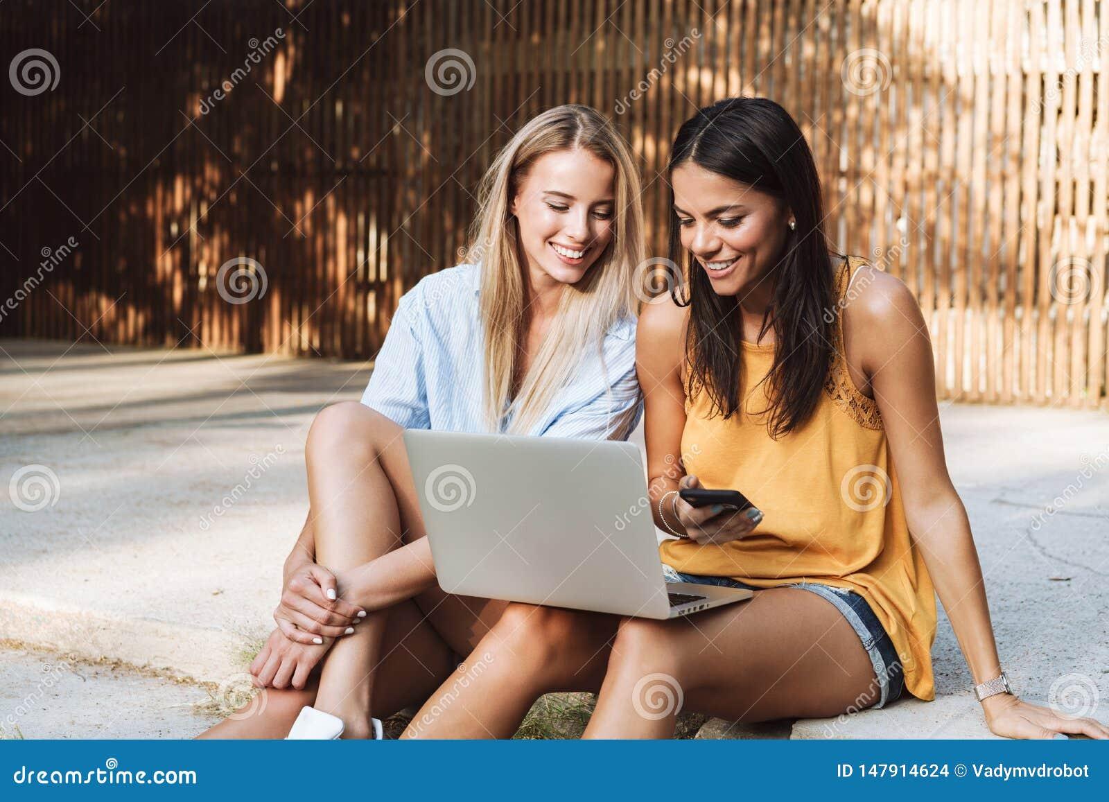 Dwa u?miechni?tej m?odej dziewczyny u?ywa laptop przy parkiem