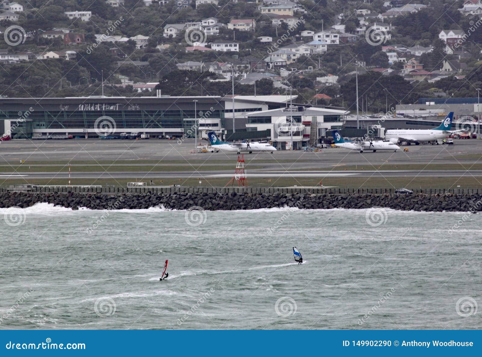 Dwa wiatrowego surfingowa na Lyall Trzymać na dystans w Wellington Nowa Zelandia na popielatym burzowym dniu Lotnisko może widzie