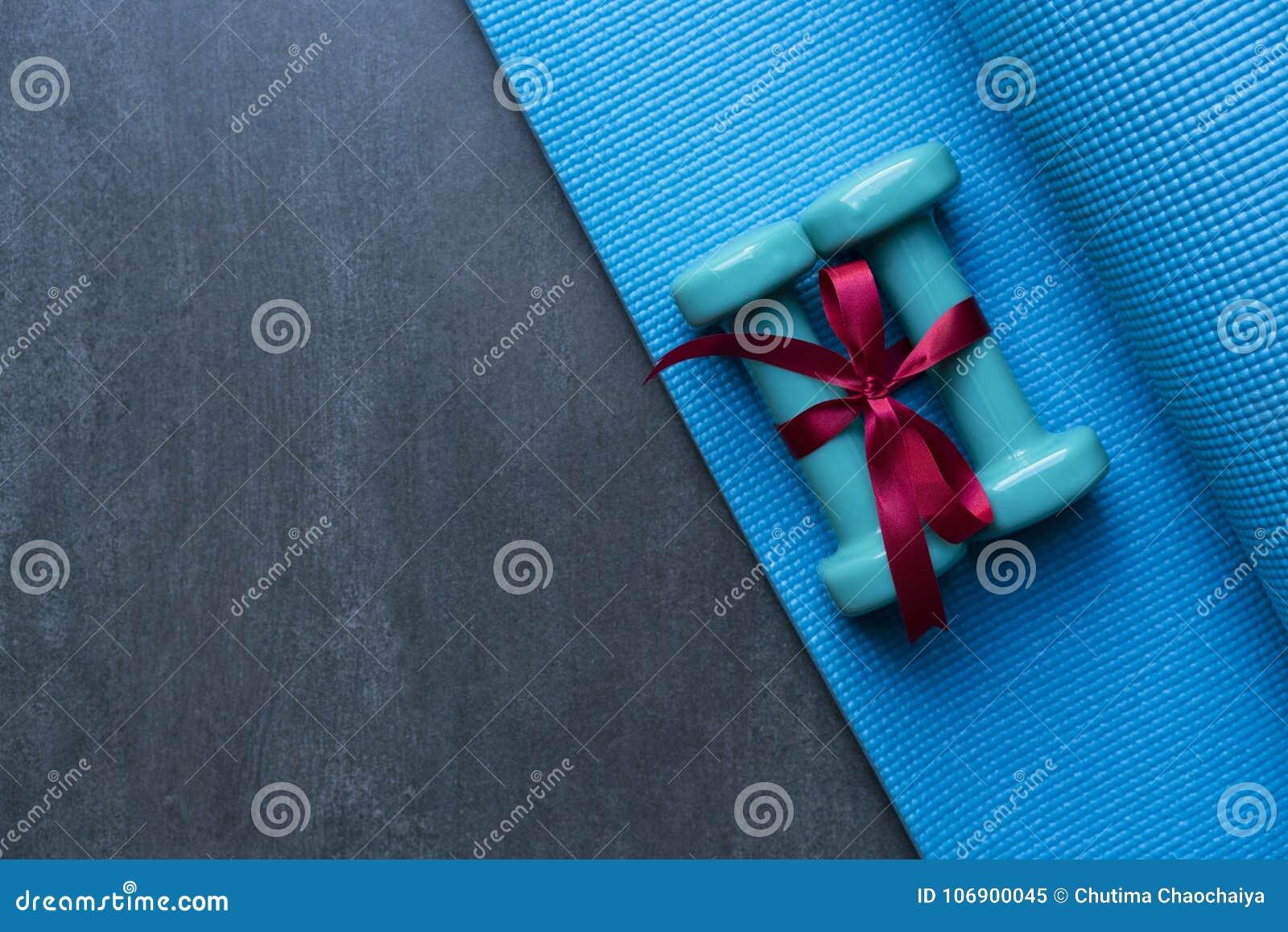 Dwa zielony dumbbell z czerwonym prezenta łękiem na błękitnej joga macie