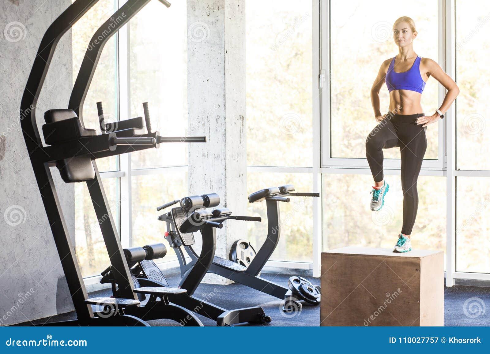 Dwars geschikt concept De vrouw in gymnastiek voert op doos op