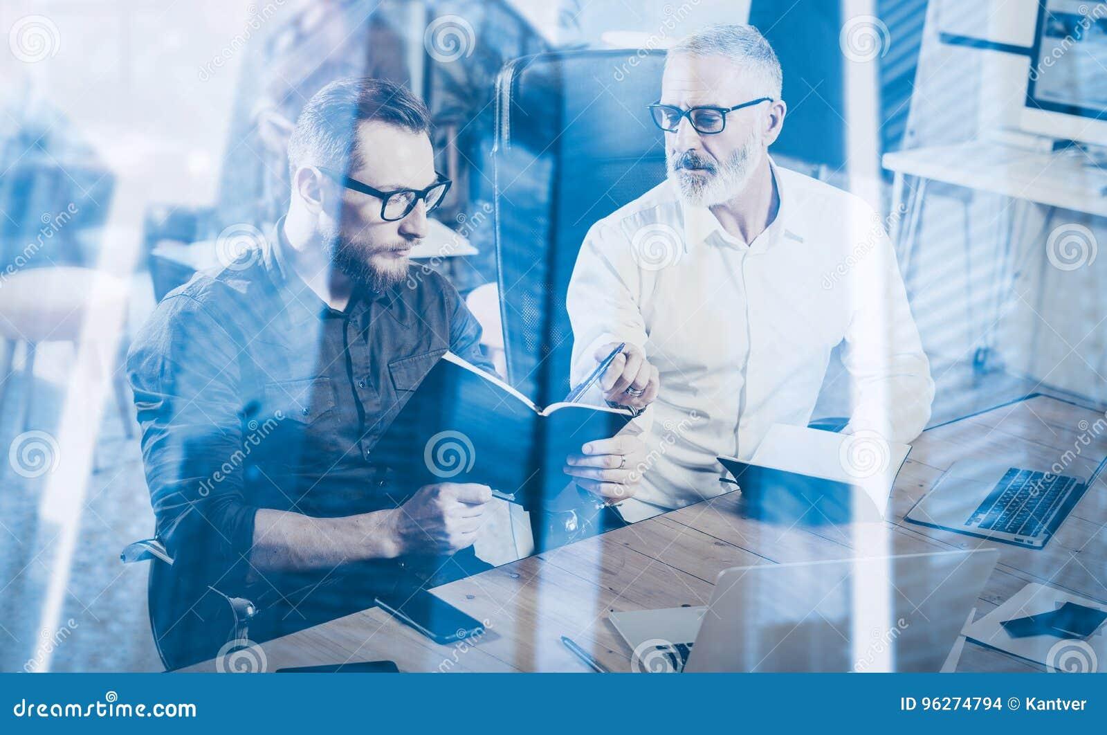 Dwoistego ujawnienia pojęcie Praca zespołowa proces w nowożytnym coworking studiu Młody brodaty mężczyzna i dorosłego biznesmen r