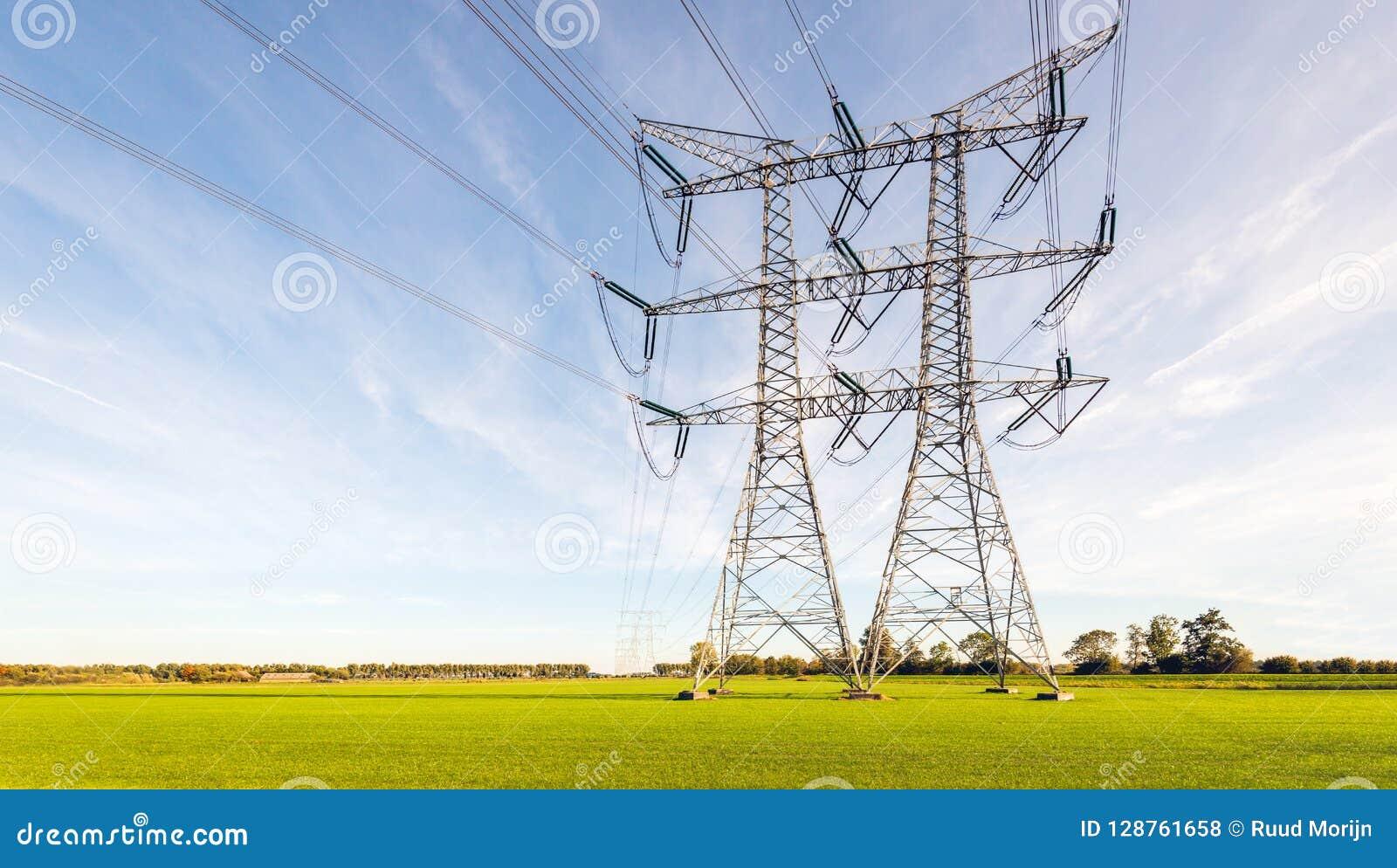 Dwoisty rząd linie energetyczne i pilony w płaskiej Holenderskiej wiejskiej ziemi