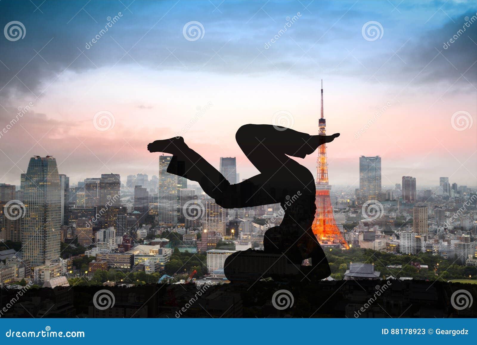 Dwoisty ujawnienie sylwetki joga kobieta przeciw Tokio miastu