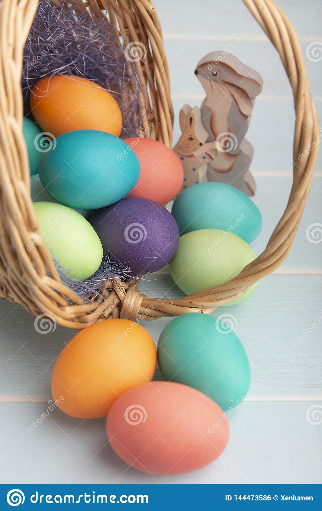 Dyed bright Easter eggs in a basket with colorful blue sisal  and wooden bunnies