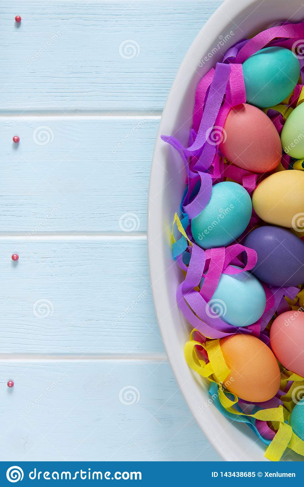 Dyed Easter eggs in a dish with colorful paper ribbons and sugar sprinkle confectionery dots
