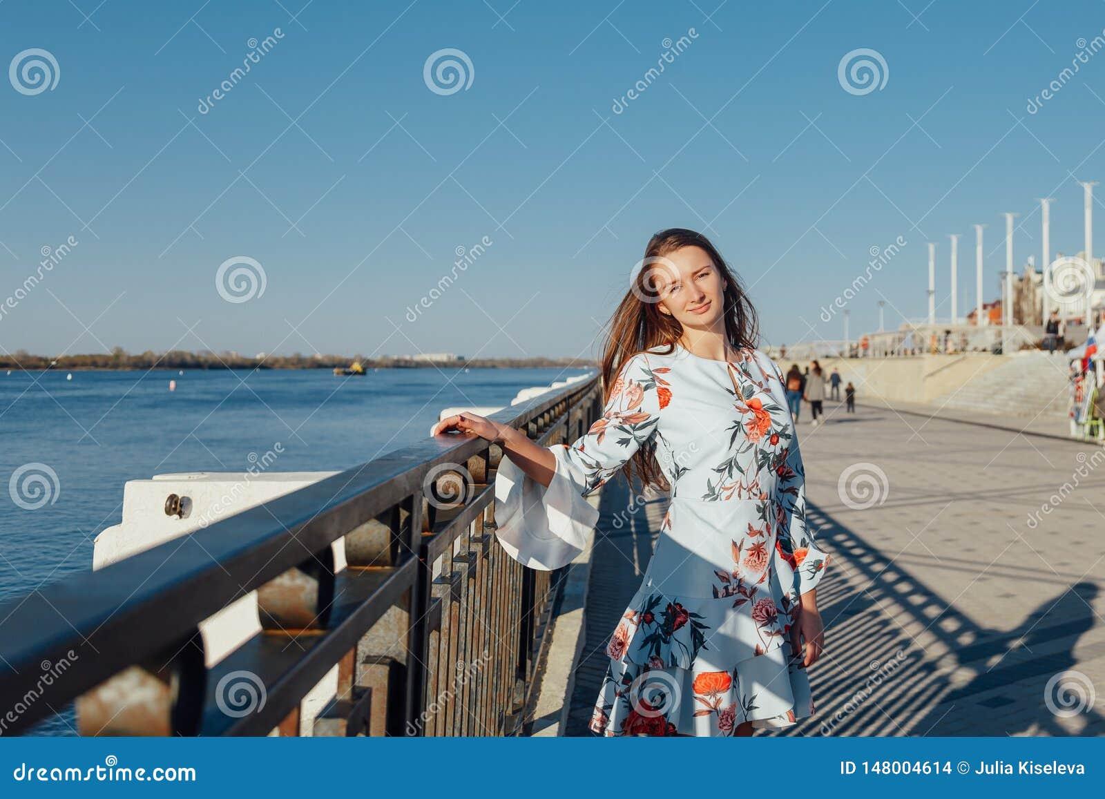 Dynamisches Modeart Porträt eines jungen schönen Mädchens, das entlang die Ufergegend der Stadt geht