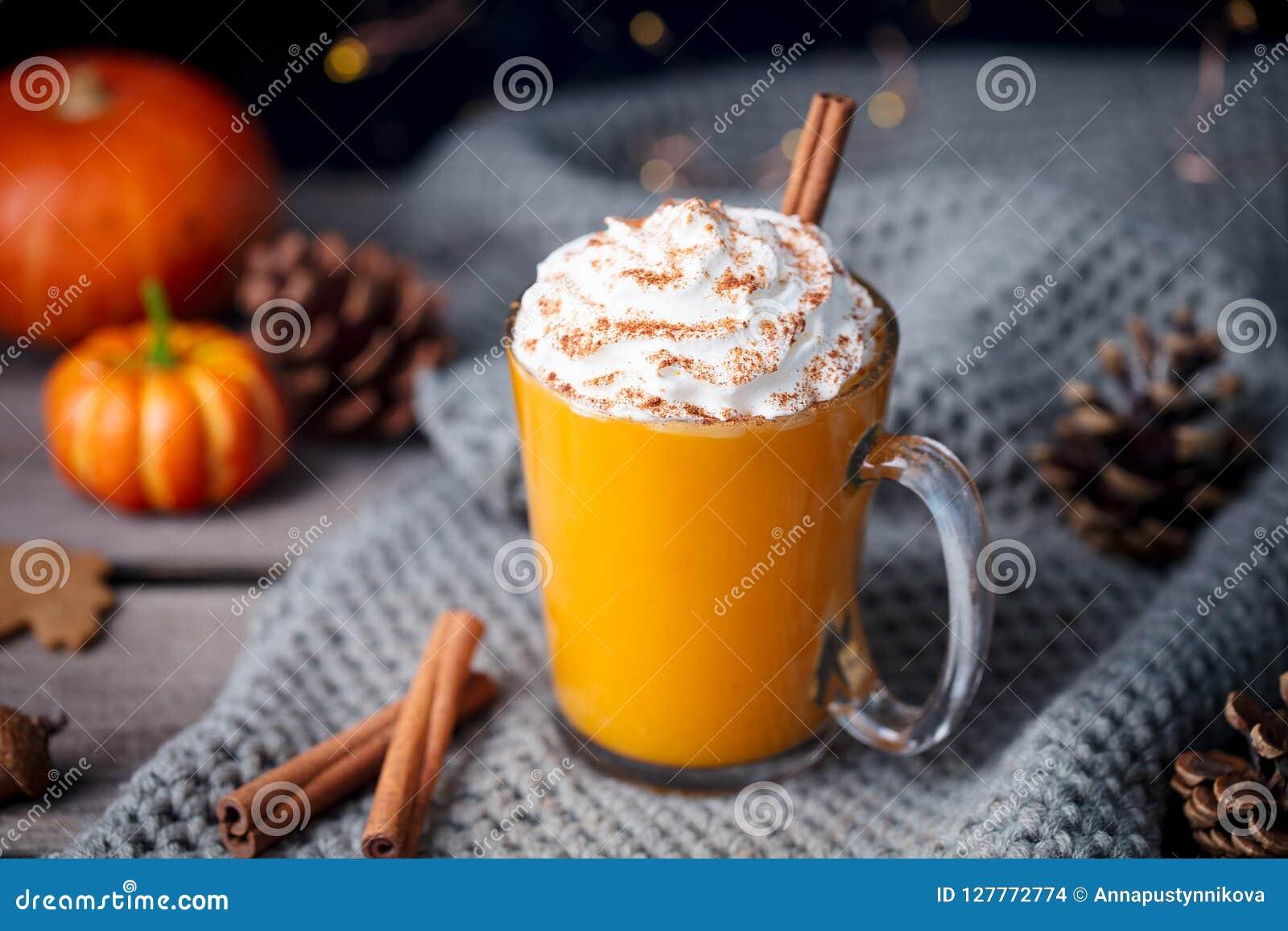 Dyniowy latte z pikantność Pijacki koktajl z batożącą śmietanką na wierzchołku na drewnianym tle