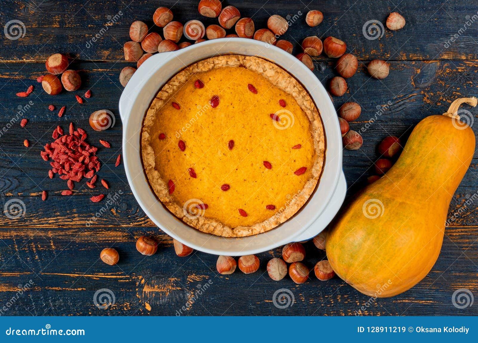 Dyniowy tarta z goji jagodą w wypiekowym naczyniu dekorował z hazelnuts na czarnym drewnianym tle Tradycyjny jesień kulebiak