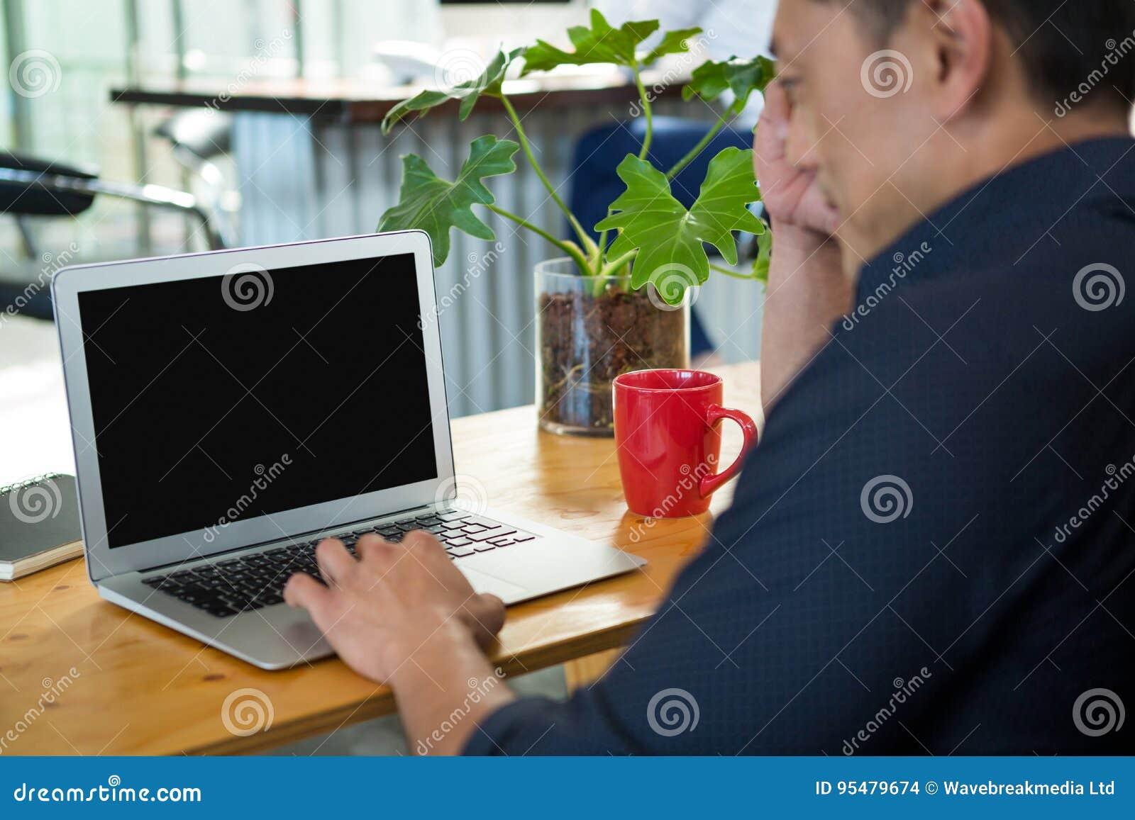 Dyrektora wykonawczego obsiadanie przy biurkiem i używać laptopem