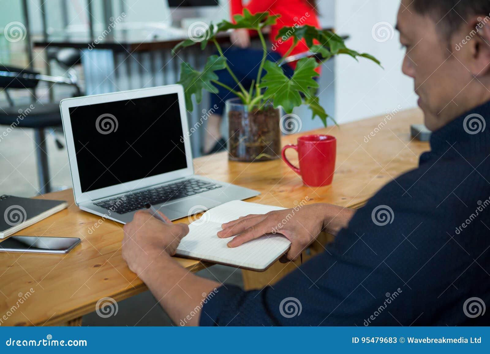 Dyrektora wykonawczego siedzący biurko patrzeje dzienniczek