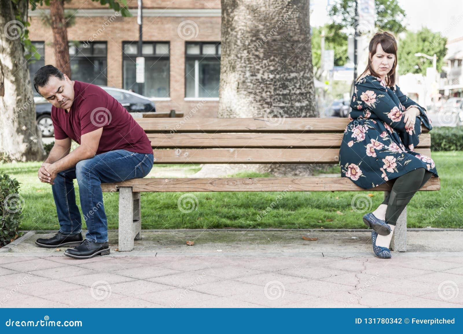 Dyskutować Mieszającego Biegowej pary Siedzącego obszycie Zdala od Each Inny na Parkowej ławce