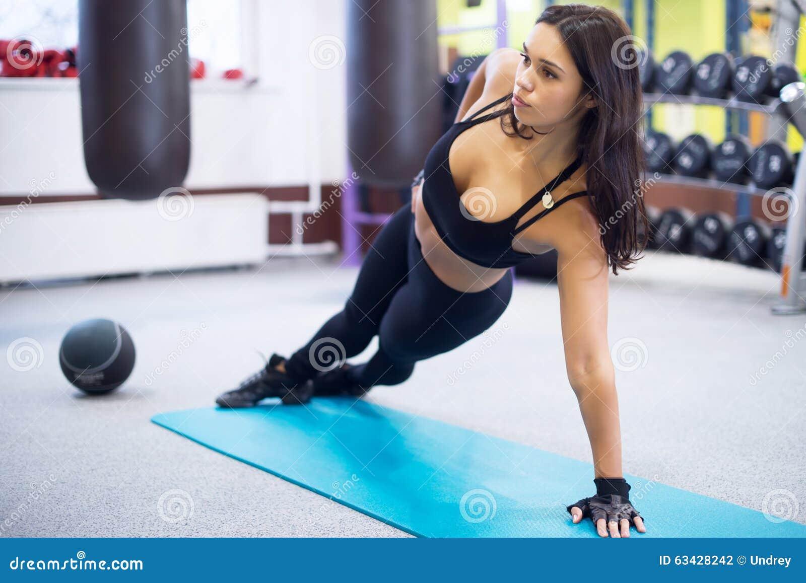 Dysponowana kobieta robi bocznemu deski joga pozy pojęciu