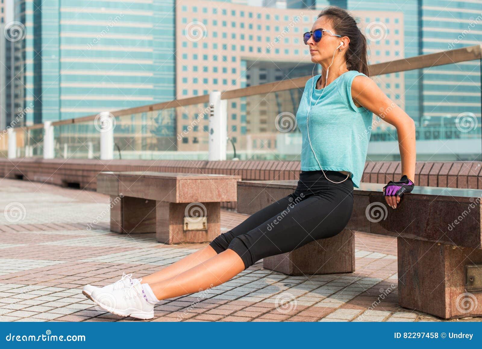 Dysponowana kobieta robi triceps ławki upadom ćwiczy podczas gdy słuchający muzyka w hełmofonach Sprawności fizycznej dziewczyna