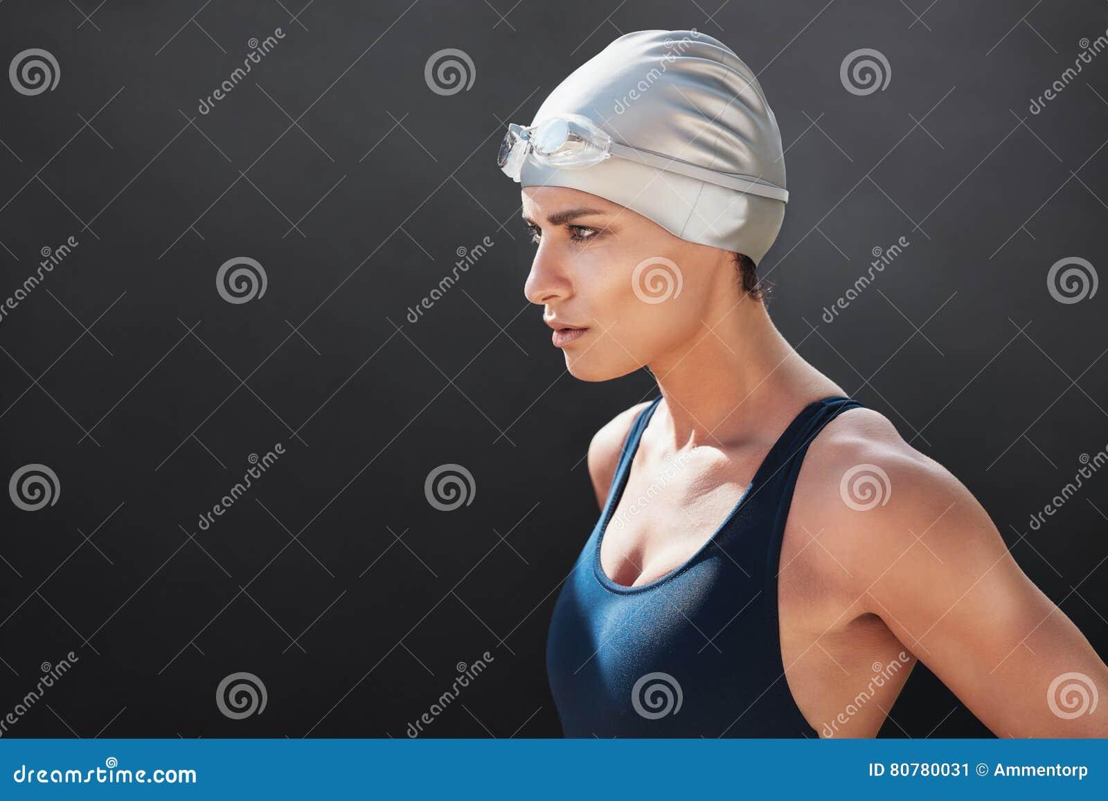 Dysponowana młoda kobieta patrzeje daleko od w pływackim kostiumu