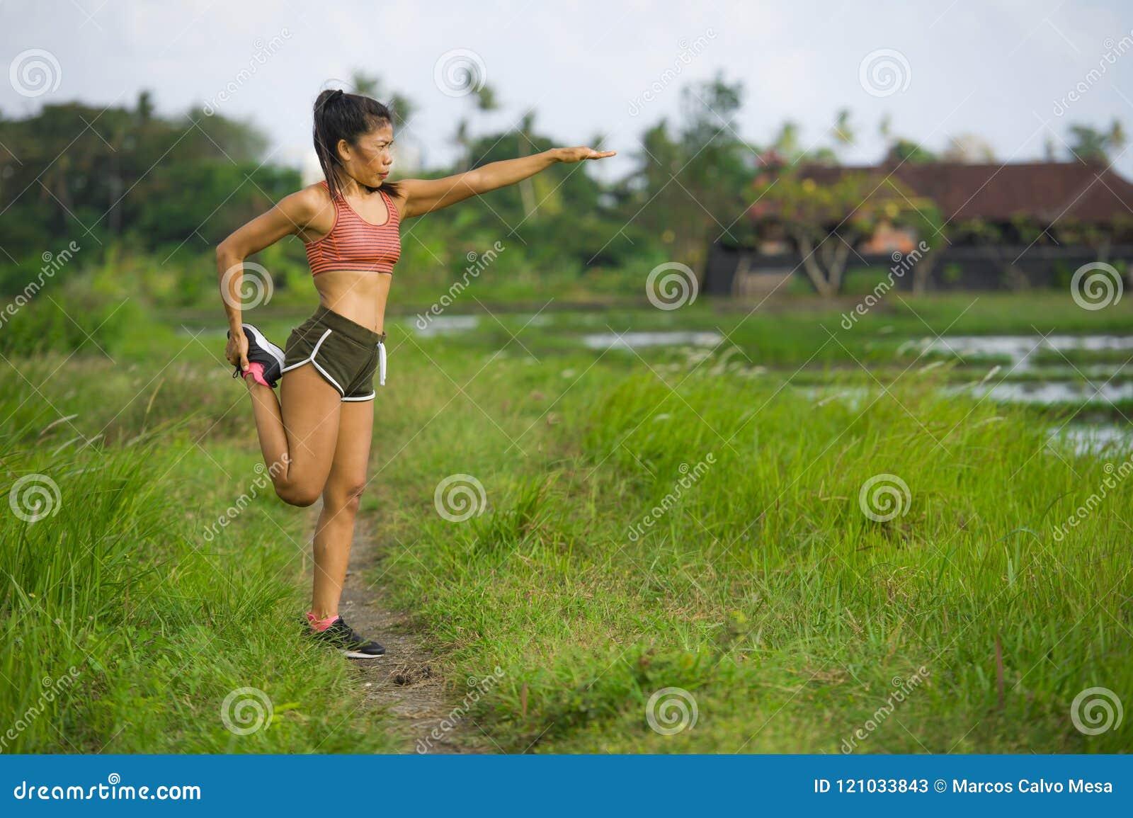 Dysponowanego i sporty biegacza kobiety rozciągania Azjatycka noga i ciało po tym jak działający trening na zieleni pola pięknym
