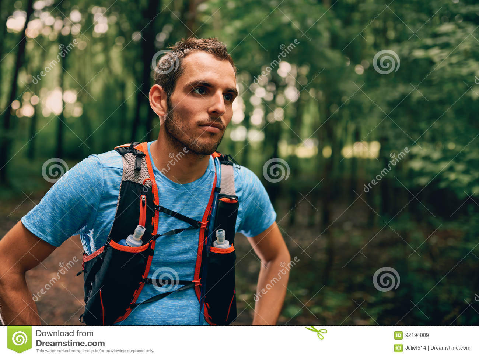 Dysponowani męscy jogger odpoczynki podczas dnia jogging dla przecinającego kraju lasowego śladu ścigają się w natura parku