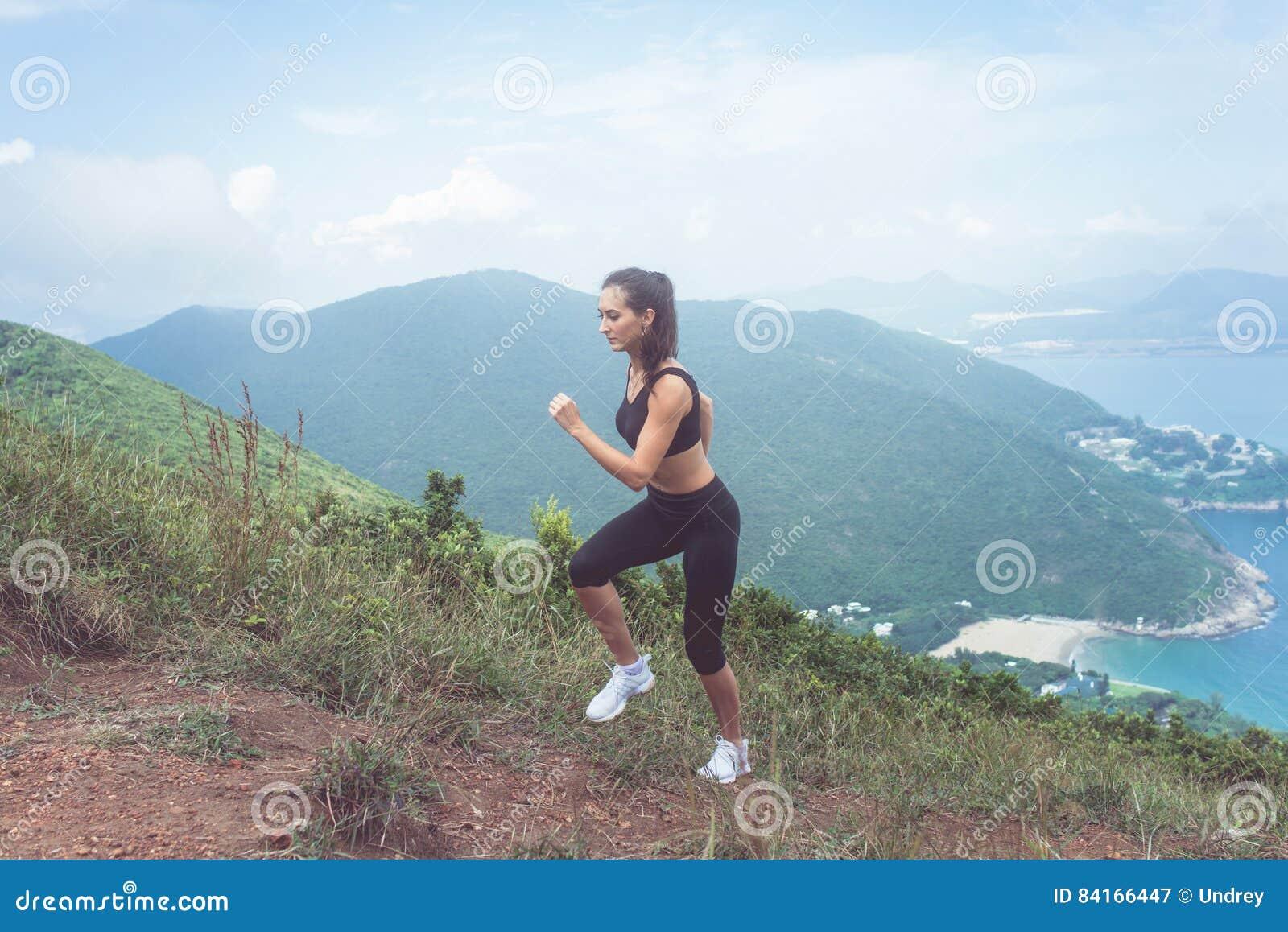 Dysponowany żeński jogger ćwiczy, biega ciężki z morzem i góry w tle,